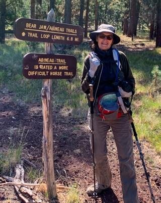 Karin standing at Abineau trailhead sign