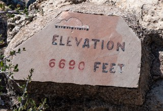 Elevation 6690 feet printed on rock sign in Walnut Canyon