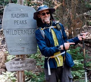 Man at trailhead sign for Abineau trail loop