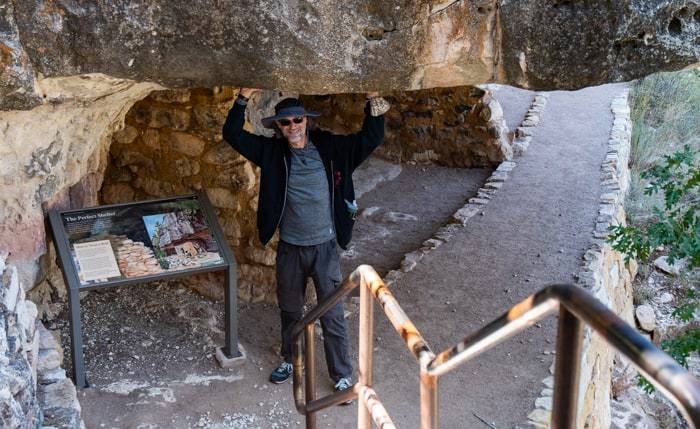 Franz holding up rock roof on Loop trail in Walnut Canyon